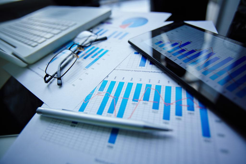 Image of eyeglasses, pen, touchpad and financial documents at workplace